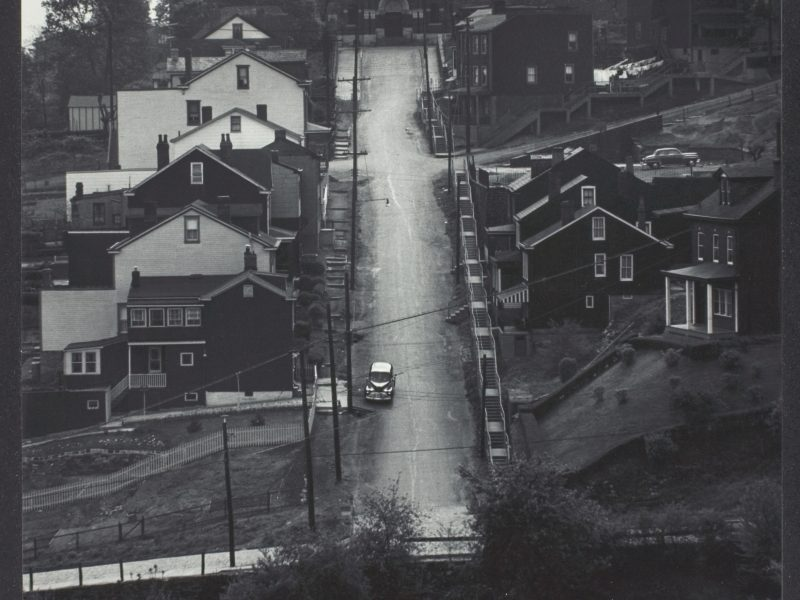 W. Eugene Smith, Street in Pittsburgh: Downhill; houses on either side; church at end of street, 1955